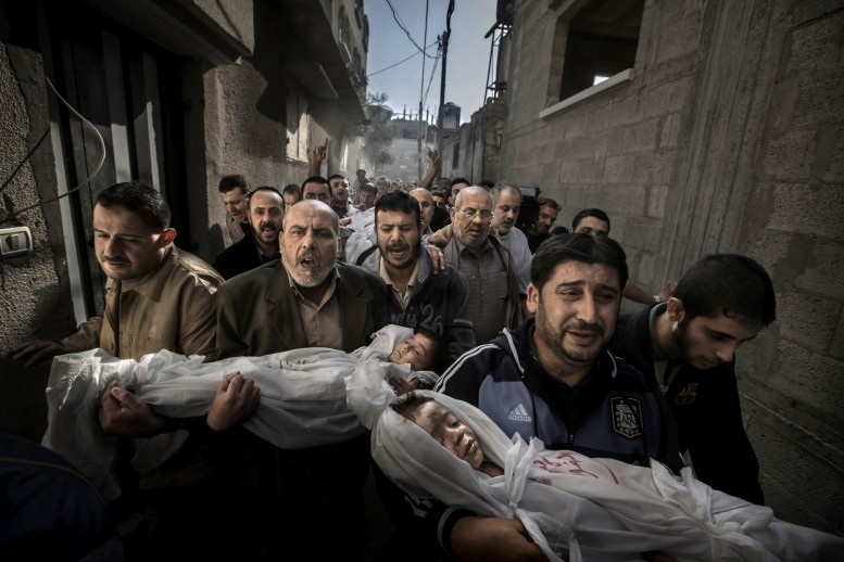 Two-year-old Suhaib Hijazi and his older brother Muhammad were killed when their house was destroyed by an Israeli missile strike. Their father Fouad was also killed and their mother was put in intensive care. Fouad's brothers carry his children to the mosque for the burial ceremony as his body is carried behind on a stretcher. Photograph by Paul Hansen