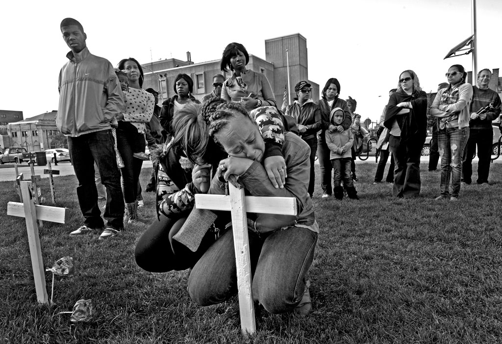At a field of crosses created to draw attention to the record homicide rate in Camden, NJ, the most dangerous city in America, Lisa Anderson cried in memory of her son, Lateaf, who was shot and killed by the jealous ex-boyfriend of a female friend. Photograph by April Saul