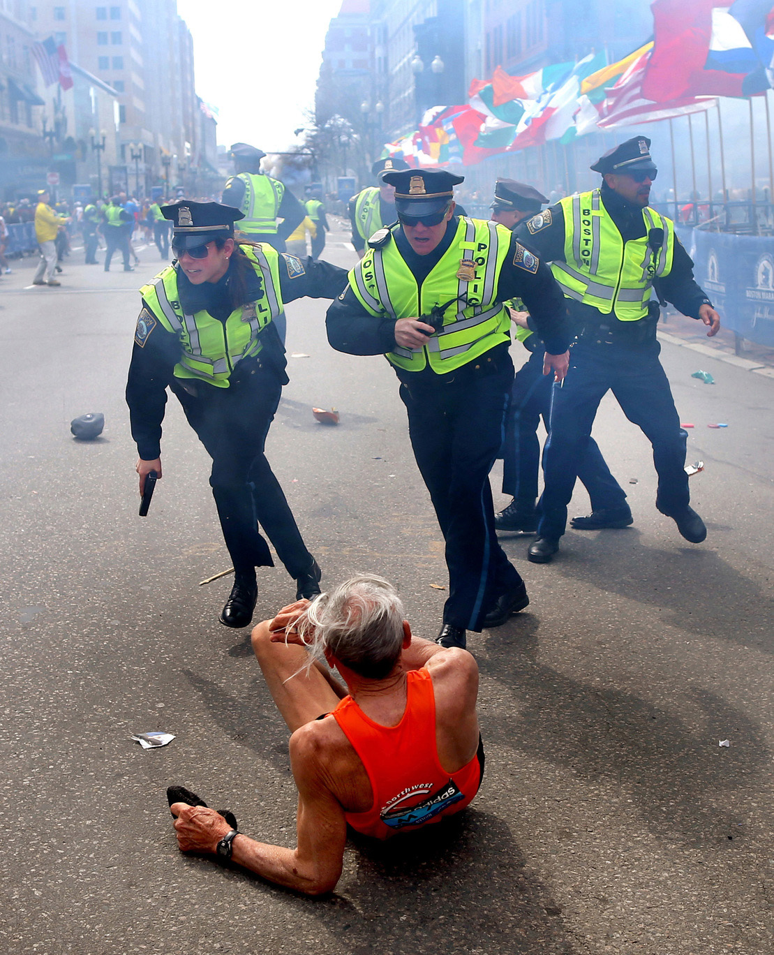 Police officers with their guns drawn heard a second explosion down the street from the finish line of the 117th Boston Marathon. The first explosion knocked down this runner. The image was part of the portfolio that won John Tlumacki the title of NPPA 2014 Photojournalist of the Year (Larger Markets). Photograph by By John Tlumacki-Boston Globe