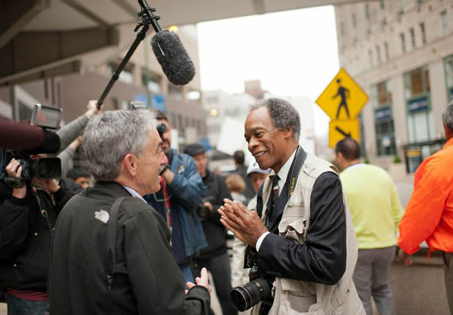 Former Sun-Times veteran photojournalist John H. White (in vest) talks with photojournalist Mark Hertzberg this morning outside the Sun-Times offices in downtown Chicago.