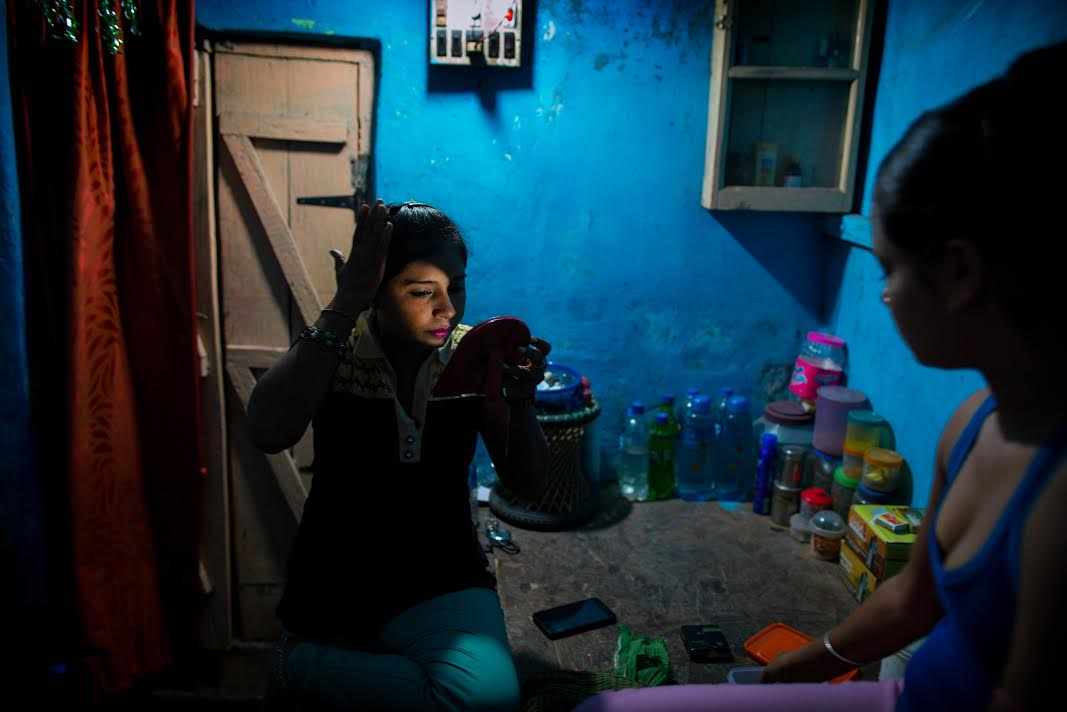 Inside the tiny room of a Kolkata brothel, Shabnam (L) and her cousin Niya (R) - both in their early twenties, they say - primp for their night of prostitution. Shadnam was beaten and forced into sex trafficking and then ordered by an abusive madam to coerce her cousin to join her. Many young girls in India fall prey to the thieving industry of sex trafficking and face impossible odds to escape it. For many 'low-caste' girls and women from nomadic cultures in India, prostitution is commonly passed down from