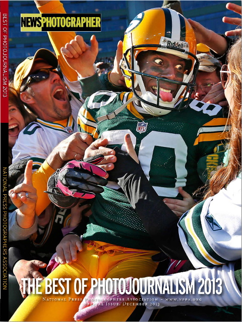 The cover of the December 2013 Best Of Photojournalism special issue of News Photographer magazine, featuring the First Place Sports Feature photograph by Mike Roemer of the Associated Press that shows Green Bay Packers Donald Driver celebrating a touchdown by doing a Lambeau Leap in Green Bay, WI