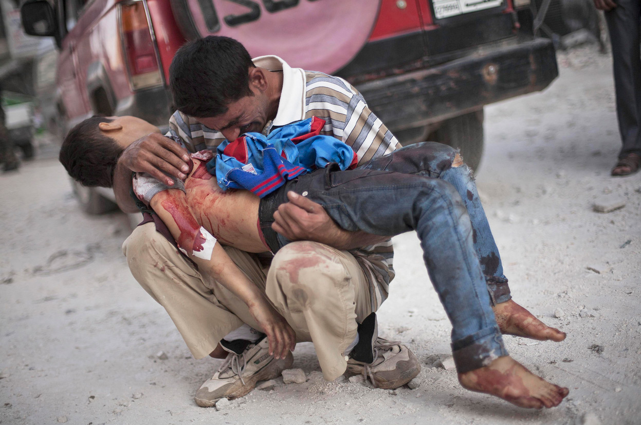 A Syrian man cried while holding the body of his son, killed by the Syrian Army near Dar El Shifa hospital in Aleppo in October. AP Photograph by Manu Brabo