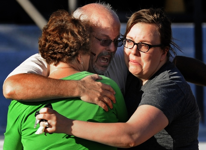 "A gunman slipped into a midnight premiere of the new Batman movie through an emergency exit, tossed two hissing gas canisters and then methodically, calmly walked up the aisle firing, killing 12 people and wounding 70. It was among the worst mass shootings in American history. Tom Sullivan, center, embraces family members outside Gateway High School where he has been franticly searching for his son, Alex Sullivan, who saw ""The Dark Knight Rises,"" in the movie theater where a gunman opened fire Friday, July"
