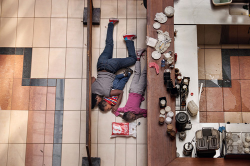 A woman and her two small children hid from Somali militants' gunfire on the floor of a cafe in Nairobi's Westgate Shopping Center. They survived the massacre, staying pinned down on the floor for more than five hours. Photograph by Tyler Hicks, The New York Times