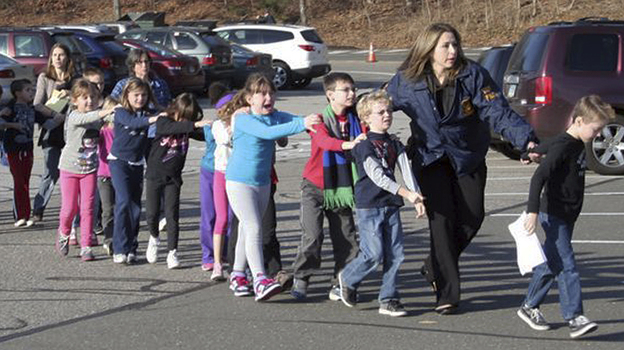 In a photograph taken by Shannon Hicks, police and teachers lead children away from Sandy Hook Elementary. Photography by Shannon Hicks/AP