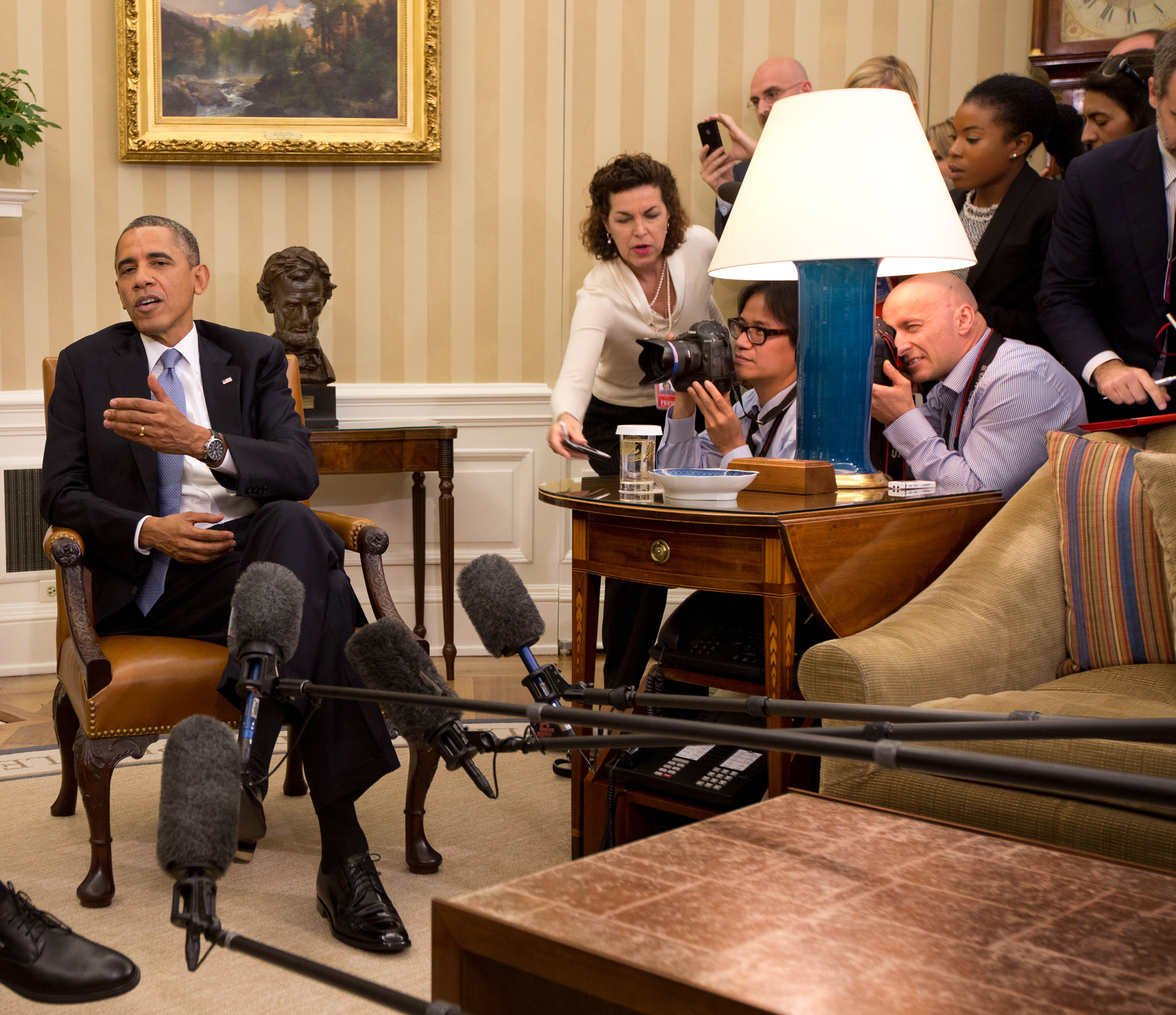 """Associated Press photojournalist Charles Dharapak and Reuters photojournalist Jason Reed try to photograph President Barack Obama during one of the Oval Office scrams, where a tight pool is ushered in for no more than a few moments to shoot an orchestrated """"photo op"""" and then just as quickly they are herded out again. Photograph by Stephen Crowley, The New York Times"""