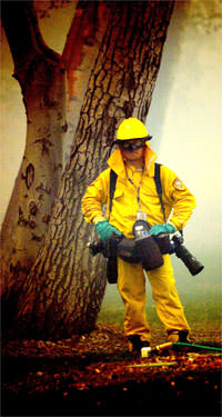 San Bernardino Sun Staff Photographer Brett K. Snow stands in the smoke wearing fire protective gear while taking a break from covering the Grand Prix fire near Lytle Creek, CA. Photo by Eric Reed/San Bernardino Sun