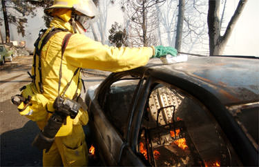San Bernardino Sun Staff Photographer Eric Reed sets two burritos down on the hot metal of a burning car to heat them for lunch while covering the Old Fire in Crestline, CA. Photo by Brett K. Snow/San Bernardino Sun