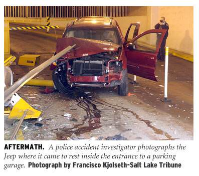 [Aftermath: A police accident investigator photographs the Jeep where it came to rest inside the entrance to a parking garage. Photograph by Francisco Kjolseth - Salt Lake Tribune]