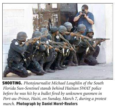 [Shooting: Photojournalist Michael Laughlin of the South Florida Sun-Sentinel stands behind Haitian SWAT police just as he was hit by a bullet fired by unknown gunmen in Port-au-Prince, Haiti, on Sunday, March 7, during a protest march. Photograph by Daniel Morel/Reuters]