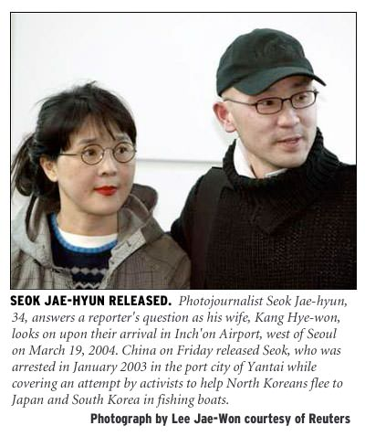 [Seok Jae-hyun Released: Photojournalist Seok Jae-hyun, 34, answers a reporter's question as his wife, Kang Hye-won, looks on upon their arrival in Inch'on airport, west of Seoul on March 19, 2004. China on Friday released Seok, who was arrested in January 2003 in the port city of Yantai while covering an attempt by activists to help North Koreans flee to Japan and South Korea in fishing boats, South Korea. Photograph by Lee Jae-won courtesy of Reuters.]