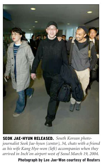 [Seok Jae-hyun Released: South Korean photojournalist Seok Jae-hyun (center), 34, chats with a friend as his wife Kang Hye-won (left) accompanies when they arrived in Inch'on airport west of Seoul March 19, 2004. Photograph by Lee Jae-won courtesy of Reuters.]