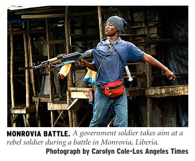 [Monrovia Battle: A government soldier takes aim at a rebel soldier during a battle in Monrovia, Liberia. Photograph by Carolyn Cole/Los Angeles Times]