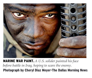 [Marine War Paint: A US soldier painted his face before battle in Iraq, hoping to scare the enemy. Photograph by Cheryl Diaz Meyer/The Dallas Morning News]