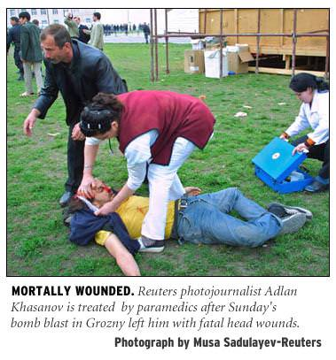[Mortally Wounded: Reuters photojournalist Adlan Khasanov is treated by paramedics after Sunday's bomb blast in Grozny left him with fatal head wounds. Photograph by Musa Sadulayev/Reuters]