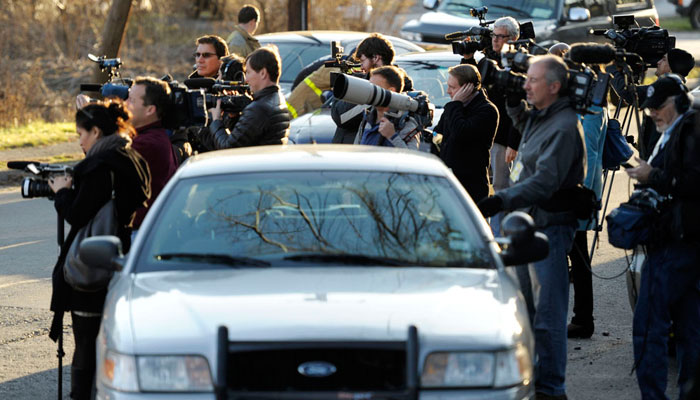 Members of the media converged on Newtown, CT, in the aftermath of the Sandy Hook school massacre (above), and resident of the small town react to the news of the killings (below). Photographs by Sean D. Elliot, The Day